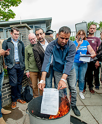 Pictured: Asylum seeker Rahman Shah burns his eviction letter from SERCO.<br /> <br /> Protesters gathered outside the main Home Office building in Glasgow to protest at private company SERCO's attempts to evict failed asylum seekers from their homes.<br /> <br /> © Dave Johnston / EEm