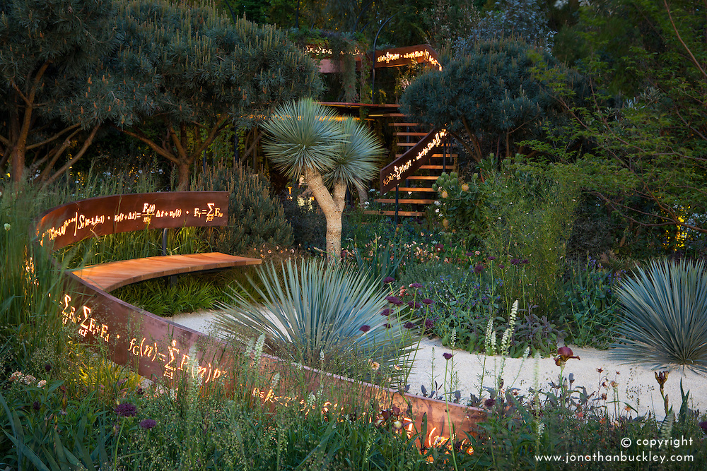The Winton Beauty of Mathematics Garden lit at night, Chelsea Flower Show 2016. Illuminated mathematical symbols cut into band of copper running through the garden forming back of bench and bannister for staircase. Pinus sylvestris 'Glauca' (blue Scot's pine),Yucca rostrata (Beaked Yucca).