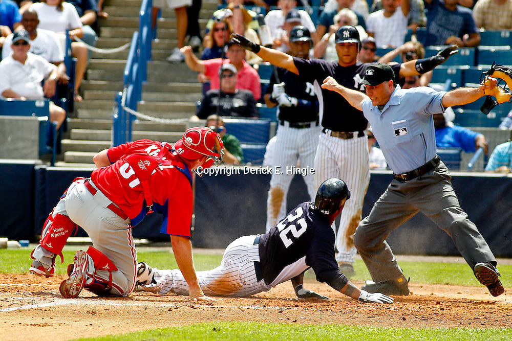 March 11, 2012; Tampa Bay, FL, USA; New York Yankees left fielder Andruw Jones (22) slides in safe past Philadelphia Phillies catcher Erik Kratz (31) scoring on a two run single by Chris Dickerson (not pictured) as homeplate umpire Dan Iassogna makes the call at the plate during the bottom of the fourth inning of a spring training game at George M. Steinbrenner Field. Mandatory Credit: Derick E. Hingle-US PRESSWIRE