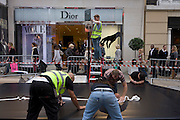 An outdoor set is constructed for the Christian Dior fashion house in London's Bond Street during Vogue's Fashion's Night Out festival in the streets of the West End. Contracted workmen show their backsides wearing high-vis tabard vests put the finishing touches to a raised ramp that a Dior-sponsored taxi cab will be placed upon, complete with fake double-yellow lines. The fake road surface is being laid out as other workmen prepare a Dior street sign and staple parts of the ramp together.