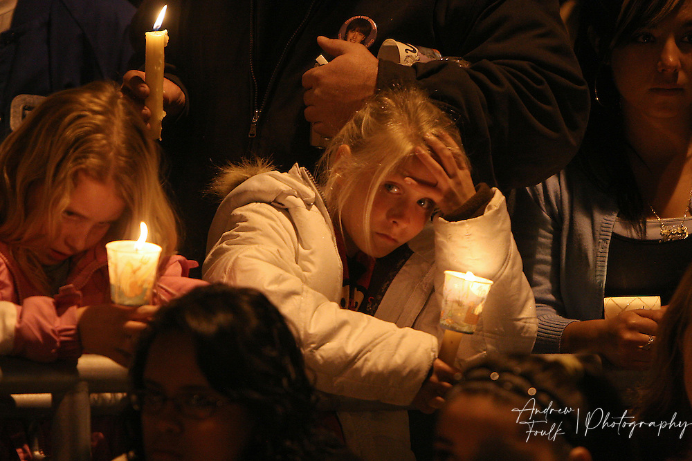 /Andrew Foulk/ For the North County Times/  .Tulalah Duncan, 10 of Vista, puts her hand on her head as a moment of silence is taken to remember Amber Dubois during a Vigil in her honor at Escondido High School Monday night.