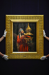 "© Licensed to London News Pictures. 11/10/2019. LONDON, UK. Technicians present ""Lighting the Lamp"", by Antonio Fabrés Y Costa, (Est GBP100-150k).  Preview of works from the Najd Collection of orientalist paintings at Sotheby's in New Bond Street, which record daily life in the historic Arab, Ottoman and Islamic worlds  All 155 paintings are on public view 11- 15 October, with 40 works to be auctioned on 22 October.  Photo credit: Stephen Chung/LNP"