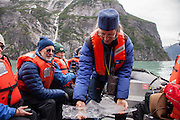 Lindblad-National Geographic Expeditions' Naturalist David Stephens shows guests from the National Geographic Sea Lion glacial ice on an excursion near South Sawyer Glacier, in the Tracy Arm fjord, part of the Tracy Arm-Fords Terror Wilderness in Southeast Alaska.