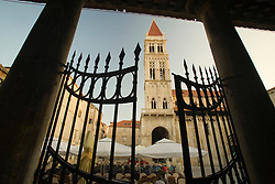 Europe, Croatia, Dalmatia, Trogir, a UNESCO World Heritage site.  Cathedral of St. Lawrence, with Venetian Gothic bell tower, built in  15th century, and outdoor cafe viewed through wrought iron gate.