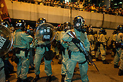 Police forces in riot gears surrounded by protesters<br /> Admiralty<br /> <br /> <br /> The streets of Hong Kong on Sunday night resemble a battleground, with police in full riot gear and gas masks firing tear gas on students wearing makeshift masks and wielding umbrellas, in the worst clashes between police and demonstrators since the 2005 WTO protests