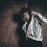 Young man 20-30 years old with dark curly hair posing in the studio with dark background