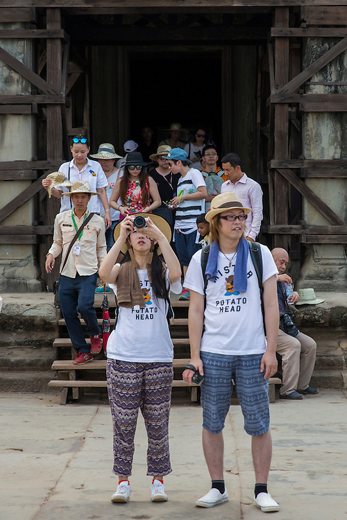 Two Asian toursits with Potato Head t-shirts outside one of the doorways in the ancient Angkor Wat temple grounds Siem Reap, Cambodia.  Angkor Wat is one of UNESCO's world heritage sites. It is Cambodia's main tourist attraction and there are lots of tourists in the background.  (photo by Andrew Aitchison / In pictures via Getty Images)