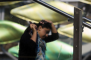Young woman brushes her hair on station steps. Behind her are the panels of the new Olympic kinetic artwork called the Shoal at Stratford. 'The Shoal' at the Stratford Centre, east London, is made up of around 100 titanium clad 'leaves' mounted between 15 and 19 metres high on metal posts. Worth £13.5m, the Shoal is part of The Stratford Town Centre Public Realm Project, designed and manufacturered using 3D technology.