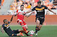 Mar 6, 2016; Houston, TX, USA; Houston Dynamo midfielder Ricardo Clark (13) slide tackled New England Revolution forward Diego Fagundez (14) while defender David Horst (18) defends in the second half at BBVA Compass Stadium. Houston Dynamo tied New England Revolution 3 to 3. Mandatory Credit: Thomas B. Shea-USA TODAY Sports