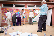 08/09/2015 - Lisbon, Portugal: António Rodrigues, 72, checks his stencil, while other participants of Lata 65 paint the wall. Lata 65 was project created by Lara Seixo Rodrigues and is a creative workshop teaching street art to senior citizens. (Eduardo Leal)