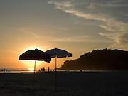 Beach umbrellas silhouetted against the setting sun at Juquhy Beach.