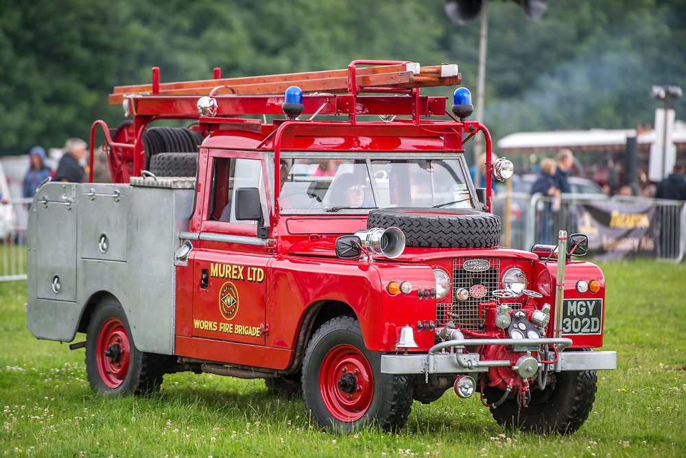 Side view of vintage Land Rover fire brigade vehicle parked on the grass, Masham, North Yorkshire, UK