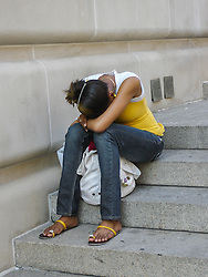 girl on steps with her head in her lap
