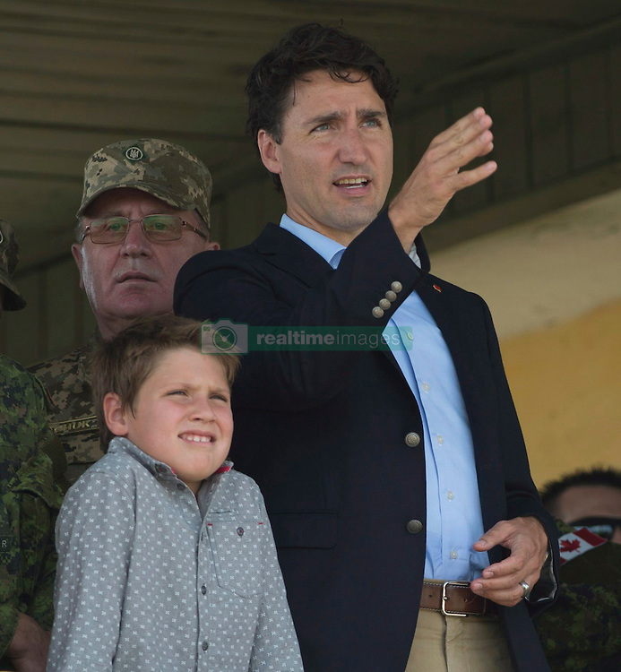 Canadian Prime Minister Justin Trudeau gestures towards a live fire demonstration as he watches with his son Xavier at the International Peacekeeping and Security Centre near Yavoriv, Ukraine Tuesday July 12, 2016. Photo by Adrian Wyld/CP/ABACAPRESS.COM  | 555273_002 Yavoriv Ukraine