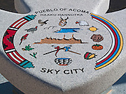 A grainite monument shaped as an arrowhead and placed at the Sky City Cultural Center displays the official seal of Acoma Pueblo.  The ring of 11 nature symbols surrounding the center designate the surviving Acoma clans.  The two crossed canes festooned with red and blue ribbons signify the gifts given by the Spanish and American governments recognizing Acoma ownership of Pueblo land and the sovereignty of the Pueblo people.