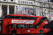 Red London Routemaster bus passes Garrick theatre showing a West End play on Charing Cross Road.