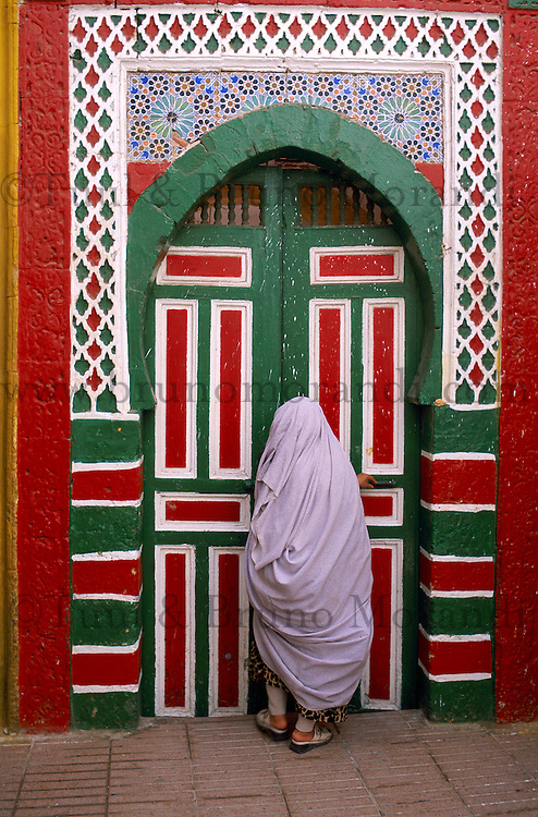 Maroc. Essaouira. Patrimone mondial de l'UNESCO. La Medina. Porte. Femme voilée. // Morocco, Essaouira, Unesco world heritage list, veiled woman with colorfull door.