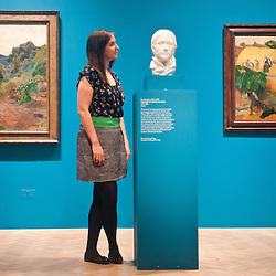 London, UK - 19 June 2013: Hannah Talbot, marketing managar at the Courtauld Gallery, stands next to ?Portrait of Mette Gauguin 1879-1880? one of only two   marble  sculptures   ever created by Paul Gauguin at the Courtauld Gallery. On the background ?Martinique landscape 1887? (L) and ?Les Meules  (The Haystacks) 1889? (R)
