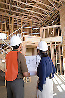 Architect and construction worker looking up while holding with blueprints inside half constructed house