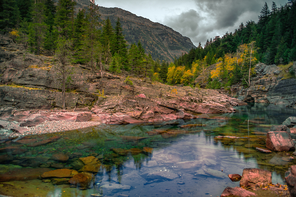 Serene glacial waters of McDonald Creek carry green tints and highlights in the early Fall Rain.