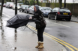 © Licensed to London News Pictures. 03/01/2012. London, UK. A women battles heavy rain and winds on Pettswood High Street, London on January 3rd, 2012. The Met Office has issued a severe weather warning as heavy rain and 85mph winds battered Britain. Photo credit : Grant Falvey/LNP