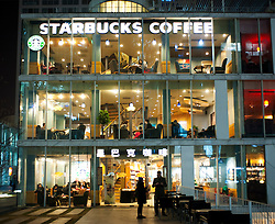 Night view of large Starbucks store in new modern Central Business District of Beijing China