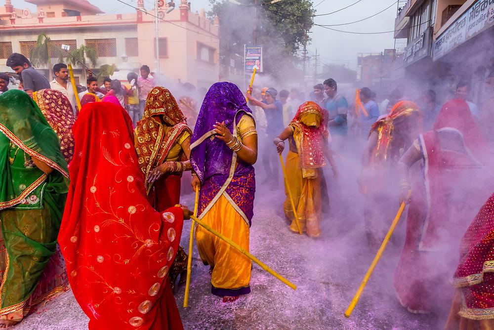 Women with lathis (sticks )chasing and beating men, Holi (festival of colors), Mathura, Uttar Pradesh, India.