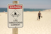 A warning sign cautions beach goers of a dangerous riptide, as a swimmer walks to the sea in the distance, Chatham Beach, Cape Cod National Seashore, Chatham, Massachusetts.