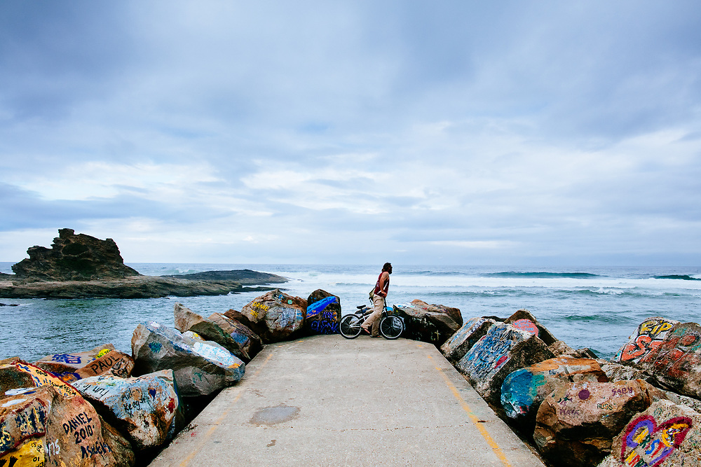 At bike rider checks surf the end of the iconicically colourful V-Wall in Nambucca Heads after a rainy day.