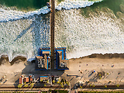 Aerial photo of San Clemente, its pier and breaking surf in Southern California.