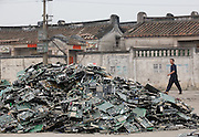 A man walks past a heap of circuit boards and other discarded electronics in Guiyu in southern China's Guangdong province.  Each year, between 20 and 50 million tons of electronic waste is generated globally. Most of it winds up in the developing world. Some of the most popular destinations for dumping computer hardware include China, India, and Nigeria. It can be 10 times cheaper to ship waste to China than to dispose of it properly at home. With the market for e-waste expected to top $11 billion by 2009, it's lucrative to dump on the developing world.
