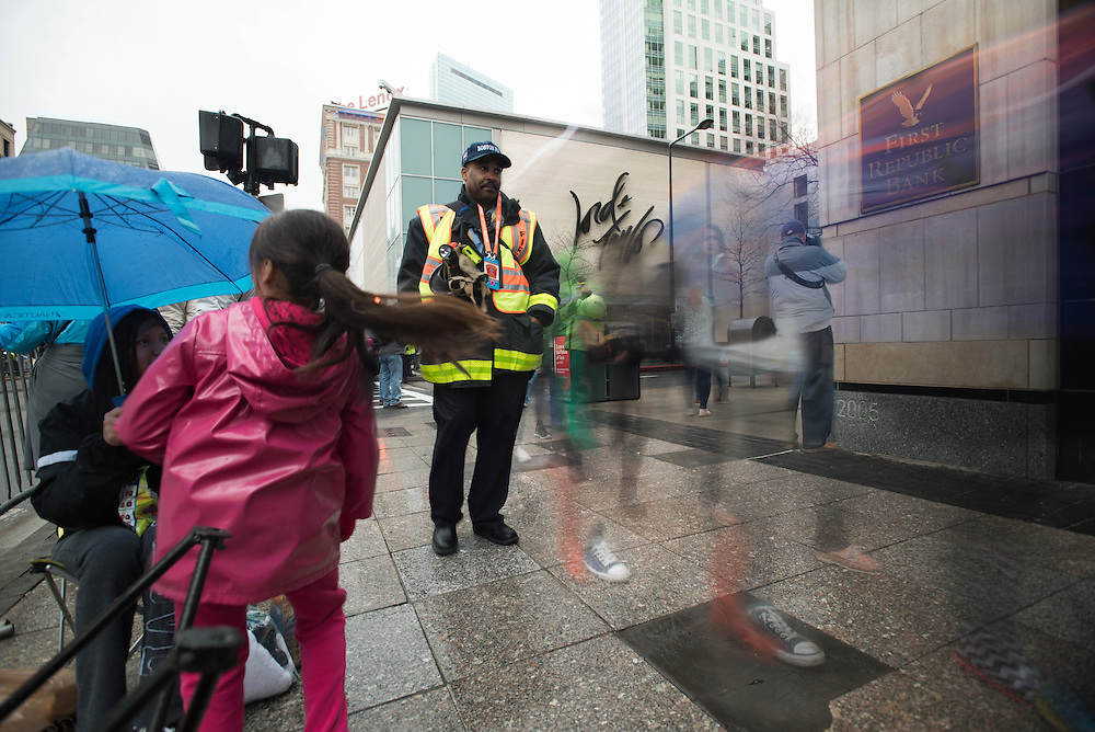 Taken Monday, April 20th, 2015 from 9:15-9:28AM.  Found and &copy; by Mike Ritter.<br /> <br /> This was Marathon Monday 2015.  The weather was rainy.  A kind fellow spectator passed me a plastic bag to place over my camera.  While I shot, the announcements of the beginning heats of runners were announced.  A fireman walks through the crowd with police officers in the background.  A photographer takes photos up Ring Road where a security checkpoint was.  A camera hangs off the roof of Lord and Taylor.  The second bomb went off almost directly across Boylston St.  Maybe that camera helped track down the Tsarnaev brothers.