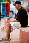 16 OCTOBER 2011 - PHOENIX, AZ: An Occupy Phoenix protester rests on a planter during the protest in Phoenix, AZ, Sunday. About 200 people continued the Occupy Phoenix protest in downtown Phoenix Sunday afternoon. The protest peaked Saturday afternoon at about 2,000 people. Nearly 50 people were arrested late Saturday night on misdemeanor trespassing charges when they tried to camp in a park near downtown and on Sunday the crowd dwindled to 200. Protesters hope to continue the protest through Monday by marching around downtown and picketing banks in the area.    PHOTO BY JACK KURTZ