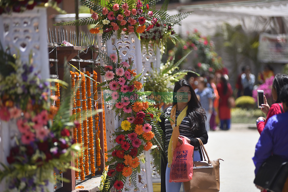 April 13, 2018 - Kathmandu, NP, Nepal - A Nepalese women pose for the photo around the decorated flowers during 21st Flora Expo 2018 at Kathmandu, Nepal on Friday, April 13, 2018. It is a yearly floriculture expo held in Nepal by FAN (Floriculture Association of Nepal) for four days. (Credit Image: © Narayan Maharjan/NurPhoto via ZUMA Press)