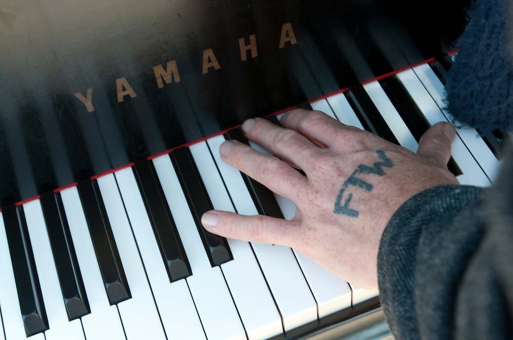 "The tattoo of FTW on Colin Huggins' hand, which stands for ""fuck the world,"" is in stark contrast to the classical implication of the Yamaha logo on his baby grand piano."