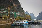 Tourist boats moored on the Li River at Yangshuo by a hotel construction site, China