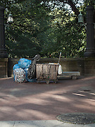 A cart and large bags filled with cans waiting to be recycled are on the red brick sidewalk on Central Park West in Manhattan, New York City