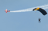 New Windsor, New York - Mike Wiskus flies the Lucas Oil Pitts S-1-11B around a member of the Black Knights West Point Parachute Team at the New York Air Show at Stewart International Airport on Aug. 30, 2015.