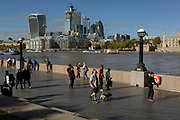 Riverside visitors walk along the Southbank with the City of London skyline (the capital's financial district - aka the Square Mile and on the far right, the Tower of London across the river Thames on the Southbank, on 26th September 2018, in London, England.