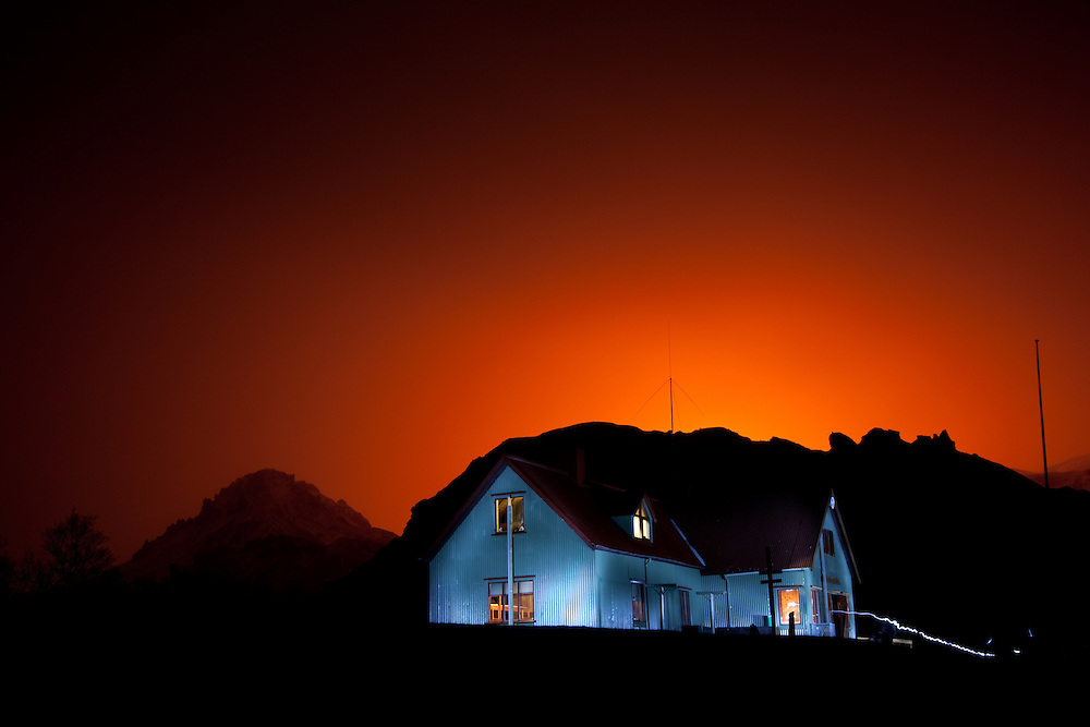 The glow from Eyjafjallajokull volcano lights up the sky behind a thorsmork mountain hut