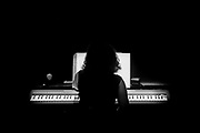 Silhouette of a woman playing a piano organ