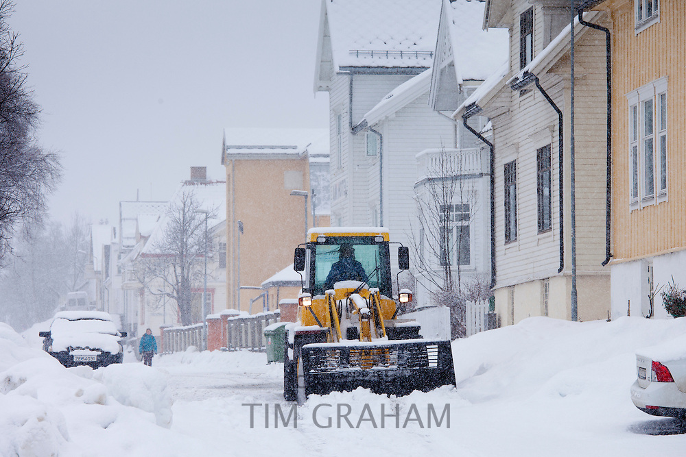 Worker drives Komatsu WA90 snow plough to clear the road in Skolegata in city of Tromso, in the Arctic Circle in Northern Norway