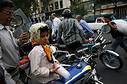 Mahtab, who is only six, already covers herself as she sits on the front of her father's motorcyle, which is the family's only form of transportation.