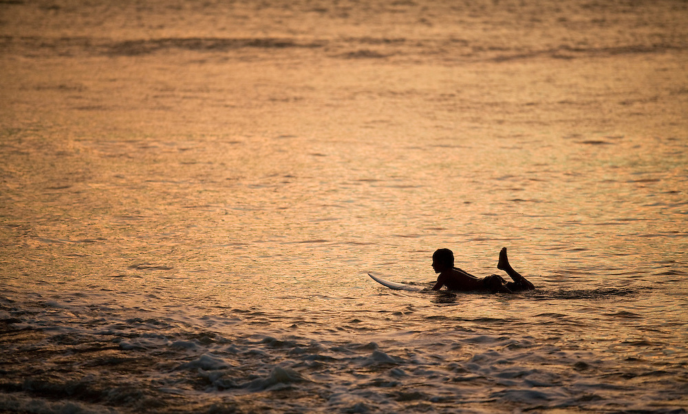 A young local surfer paddles back along the beach in Pavones to get the next wave at sunset.