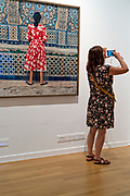 FOAM museum visitor photographing with photo Girl in Red by Yto Barrada