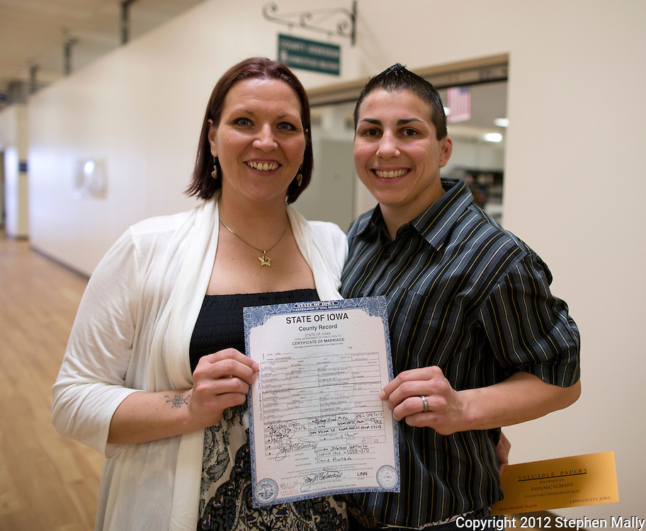 Brigg McDonald (from left) and Stephany Lee hold up their certificate of marriage at Linn County West in Cedar Rapids on Monday, April 23, 2012.