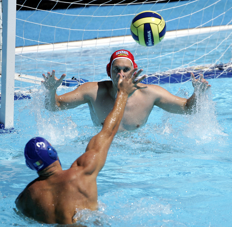 Romania's Florin Musat (L) scores a goal on Russia's goalkeeper Alexander Federov during their Classification 5-8  match at the FINA World Championships in Montreal, Quebec Thursday 28 July, 2005. Romania deafeated Russia 11-7.