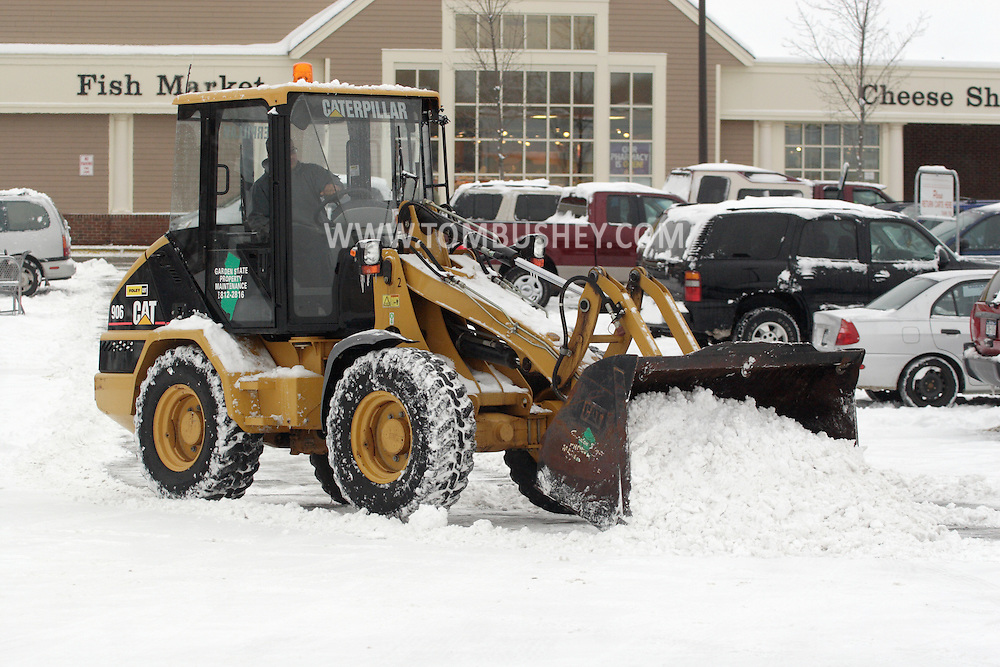 Middletown, NY - A worker uses a front end loader to clear snow from a grocery store parking lot after a snowstorm on Feb. 22, 2008.