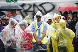 © Licensed to London News Pictures. 28/08/2016. London, UK. Spectators take shelter from the rain whilst watching the parade on family day of Notting Hill Carnival in west London, Sunday, 28 August 2016. Photo credit: Tolga Akmen/LNP