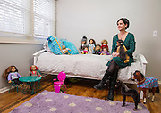 Ann Carrns, of Fayetteville, Ark., sits in her daughter's room among a collection of American Girl doll's and accessories on Friday, March 13, 2015, in Fayetteville, Ark. Photo by Beth Hall